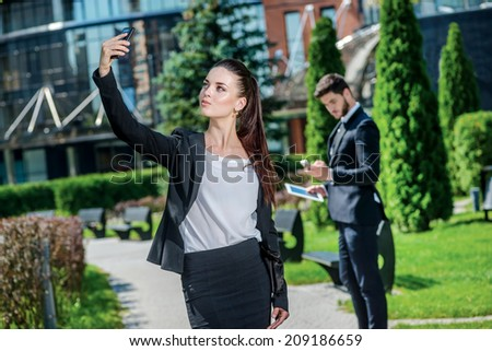 Business Selfie . Successful business woman photographing themselves by mobile phone. Businessman standing on the background and working on tablet - stock photo