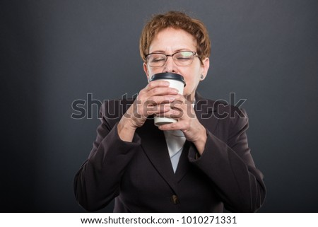 Business senior lady enjoying takeaway cup of coffee with eyes closed on black background with copyspace advertising area