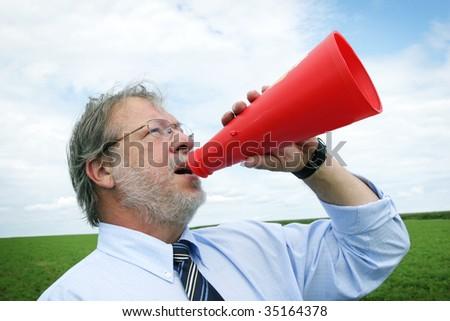 Business senior man shooting through a megaphone - stock photo
