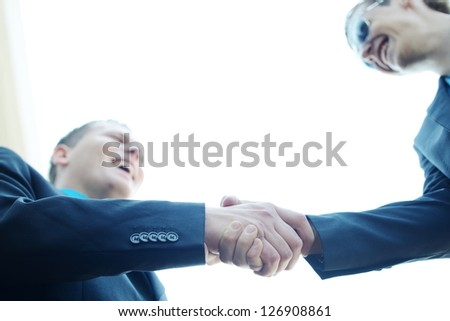Business shaking hands in front of modern building with copy space (selective focus) - stock photo