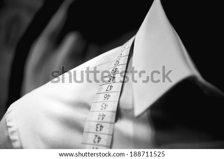 Business shirt tailoring on tailor shop mannequin with measure tape across neck  - stock photo