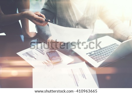 Business situation.Meeting of financial analysts.Photo female showing document.Man holding report, using laptop.Working process modern office,discussion startup. Horizontal. Film and bokeh effects - stock photo