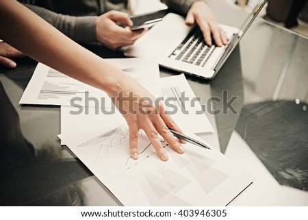 Business situation,team work. Photo female hand holding pen. Man using smartphone and modern laptop. Working process office. Discussion startup. Horizontal.Blurred,film effect