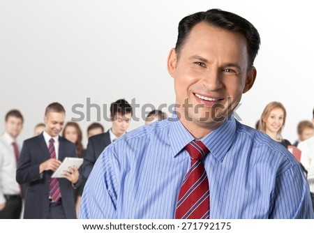 Business. Smart young businessman smiling with colleagues at the back - stock photo