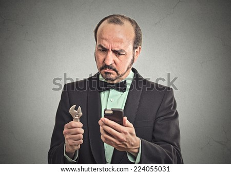 Business solution tools concept. Businessman executive looking at smartphone holding wrench key instrument in hand on office grey wall background. Face expression emotion leadership determination - stock photo