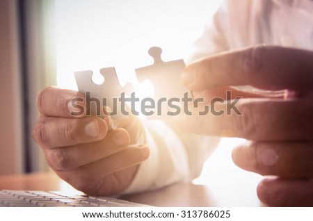 Business solutions, success and strategy concept. Businessman hand connecting jigsaw puzzle.  - stock photo