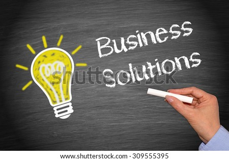 Business Solutions - yellow light bulb and female hand with chalk writing text