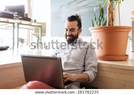 business, startup and people concept - happy businessman or creative male office worker with laptop computer networking - stock photo