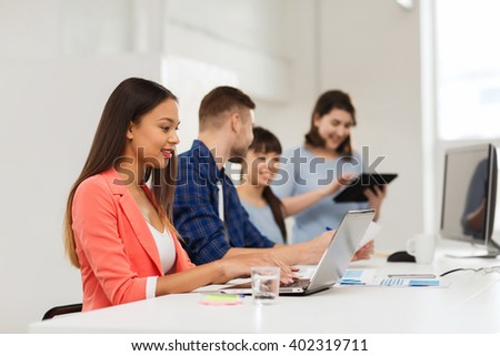 business, startup, education and people concept - happy young african woman typing on laptop computer over creative team or students working at office