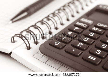 Business still-life from a notebook, a calculator and a pen on a light background.