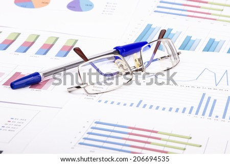 Business still-life from the table, diagram, eyeglasses, pen