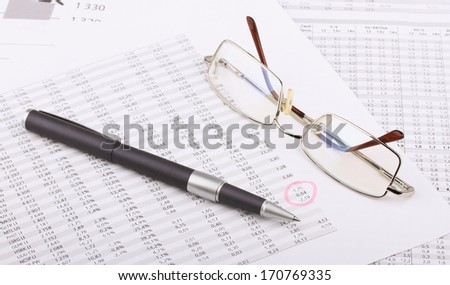 Business still-life from the table, eyeglasses, blue pen