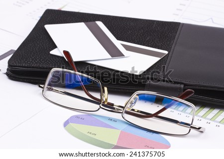 Business still-life of a charts, credit cards, eyeglasses, card holder - stock photo
