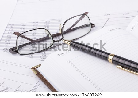 Business still-life of a charts, eyeglasses, diary