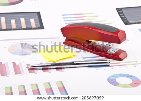 Business still-life of a charts, graphs, stapler, pen, stickers