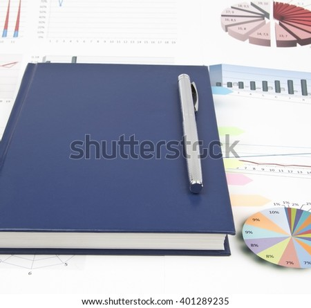Business still-life of a charts, shiny pen, diary