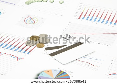 Business still-life of a coin, credit card, pin, charts - stock photo