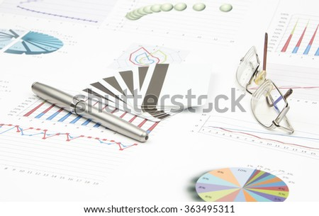 Business still-life of a credit card, pen, eyeglasses, charts