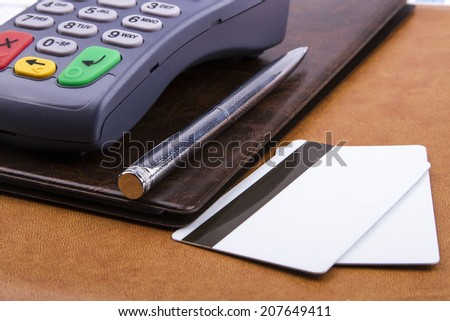 Business still-life of a payment terminal, credit cards, pen, card holder - stock photo
