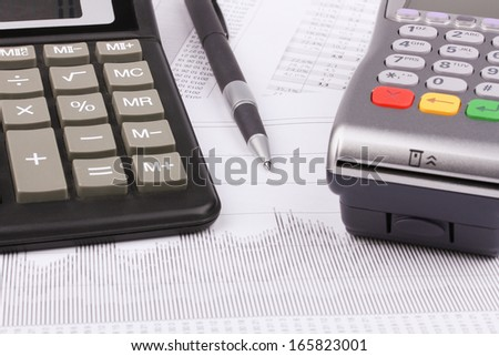 Business still-life of payment terminal, calculator, pen