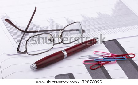 Business still-life of pen, charts, eyeglasses, graphs, clips