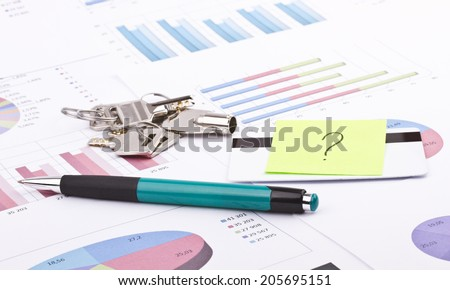 Business still-life of pen, charts, tables, shiny keys, credit card