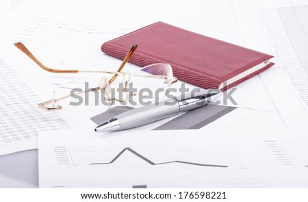Business still-life of pen, notebook, charts, eyeglasses, graphs