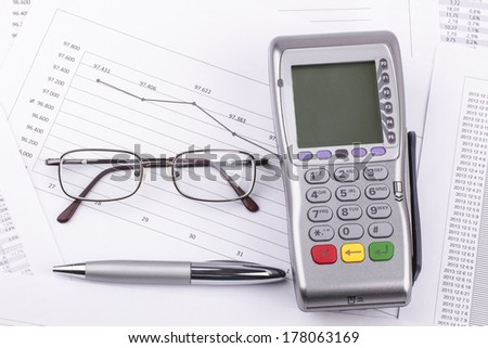 Business still-life of tables, payment terminal, credit Cards, eyeglasses, pen - stock photo