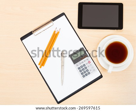business still life - view of tablet PC, clipboard, financial calculator, cup of tea, pen and pencil on office table - stock photo