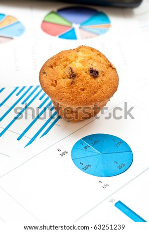Business still-life with diagrams, charts, numbers and cake - stock photo