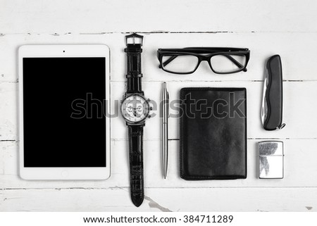 Business still-life with tablet computer glasses and cigarette lighter on white boards - stock photo