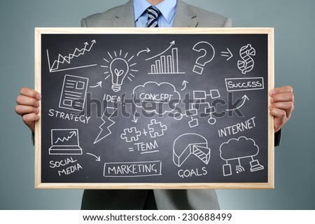 Business strategy concept businessman holding a blackboard with brainstorming chalk drawing of business creativity, imagination and inspiration - stock photo