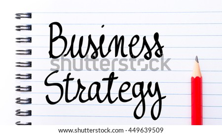 Business Strategy written on notebook page with red pencil on the right