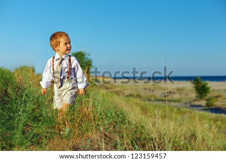 business style baby boy walking through the field near the sea