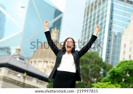 Business success - celebrating businesswoman in Hong Kong cheering business goals with arms raised up as winner. Young mixed race Chinese Asian / Caucasian female professional in Hong Kong central. - stock photo