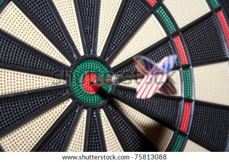 Business Success Concept - A dart with a USA flag just smacked in the center of the board. Focus on the board. - stock photo