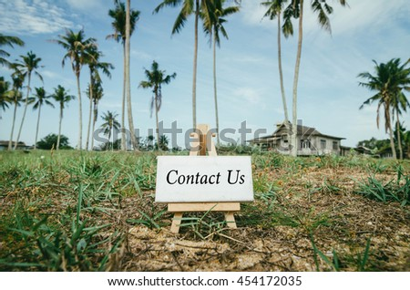 Business success concept. white canvas frame on wooden easel with word contact us over blur village  background and green grass. Wooden house surrounded by coconut tree at sunny day. - stock photo