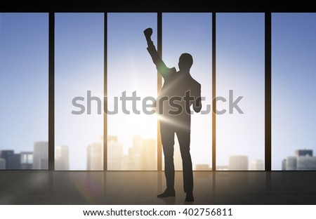business, success, gesture and people concept - silhouette of happy businessman raising fist and celebrating victory over office window background - stock photo