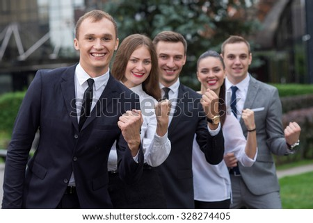 Business success. Group of young and motivated business partners are celebrating success. All are wearing formal suits. Their happy colleagues are on the background - stock photo