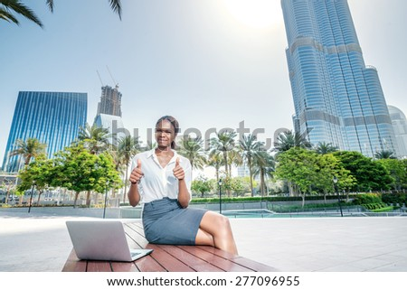 Business success in Dubai. Smiling African businesswoman businessman sitting in the street and working at a laptop in Dubai downtown among the skyscrapers showing thumbs up with both hands - stock photo
