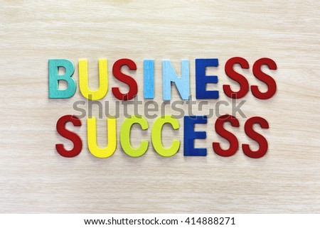 Business success in multicolor on wooden table, Letter spelling business success. Business success concept - stock photo