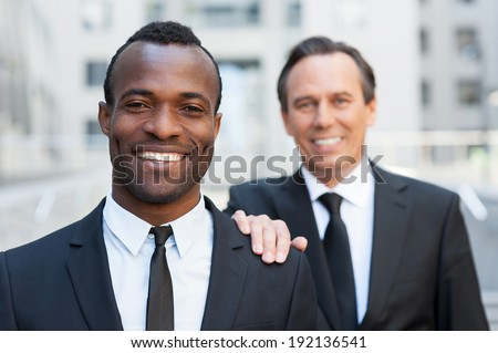 Business support. Confident senior man in formal wear holding hand on shoulder of young African man that looking at camera and smiling    - stock photo