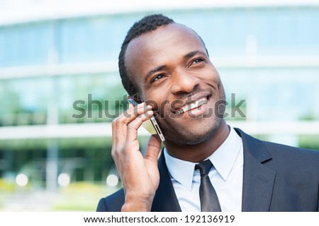 Business talk. Confident young African man in formal wear talking on the mobile phone and smiling while standing outdoors - stock photo