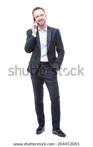 Business talk. Full length of smiling young man in suit using smart phone. Isolated on white. - stock photo