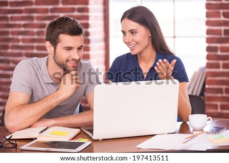 Business talk. Two cheerful young colleagues discussing something while looking at laptop - stock photo