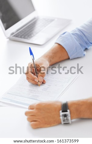 business, tax, office, school and education concept - man filling a form - stock photo