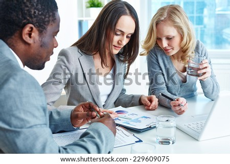 Business team analyzing financial document at meeting - stock photo