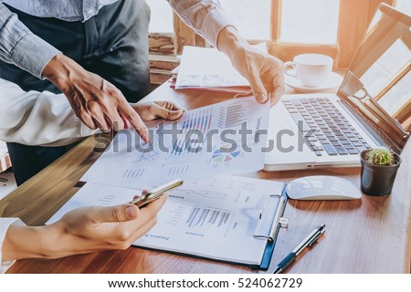 Business team analyzing income charts and graphs with modern laptop computer and using smart phone. Top view close up. Business analysis and strategy concept.