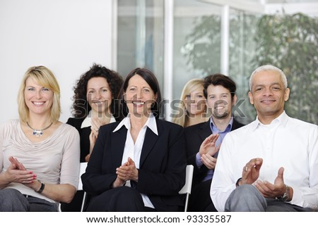 Business team applauding after a conference in a company