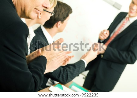 Business team applauding after a successful business presentation (selective focus only on hand in front!) - stock photo